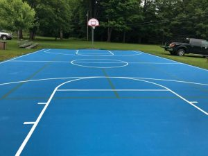 Newly resurfaced basketball court with Deco Olympic Blue; Adobe tan pickleball lines added.